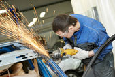 Repairman grinding metal body car — Foto Stock