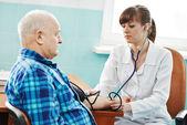 Enfermera en el examen médico la presión arterial — Foto de Stock