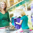 Woman with shopping cart at supermarket - Stock Photo