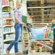 Shopping woman with cart at supermarket — Stock Photo