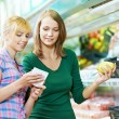 Two women at supermarket fruits shopping — Stock Photo