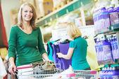Mujer con carrito de compras en el supermercado — Foto de Stock