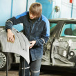 Repairman sanding plastic car bumper — Stock Photo