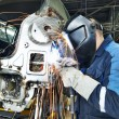 Stock Photo: Repairman welding metal body car