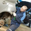 Auto repair man flatten metal body car - Stock Photo