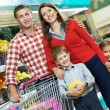 Family with children shopping fruits — Stock Photo