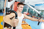 Positive man at chest exercises machine — Stock Photo