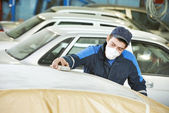 Repairman sanding automobile roof — Stock Photo