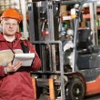 Warehouse worker in front of forklift - Stock Photo