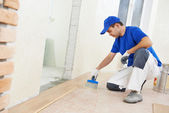Parquet worker adding glue on floor — Stock Photo