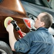 Auto mechanic polishing car - Stock Photo