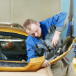 Repairman grinding metal body car - Stock Photo
