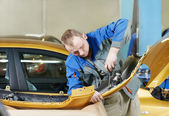 Repairman grinding metal body car — Stock Photo