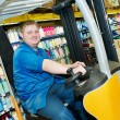 Happy warehouse worker in stacker forklift - Stock Photo