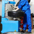 Mechanic at auto wheel tyre changer — Stock Photo