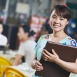 Waitress chinese girl of restaurant with menu — Stock Photo #26135905