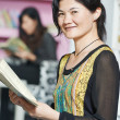 Young chinese student girl with book in library - Stock Photo