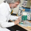 Technician engineer at work with microchip — Stock Photo #26186307