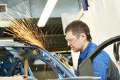 Repairman grinding metal body car — Stock Photo