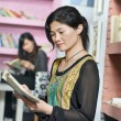Young chinese student girl with book in library — Stock Photo