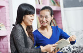 Young chinese girls with book in library — Stock Photo