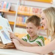 Young woman and boy reading book in library — Stockfoto