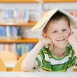 Young boy with book in library — Foto Stock