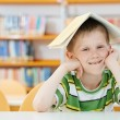 Young boy with book in library — Stock fotografie