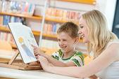 年轻女人和男孩阅读书在库中 — 图库照片