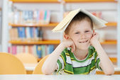 Young boy with book in library — Stock Photo