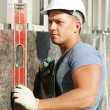 Builder facade plasterer worker with level — Stock Photo #28613633