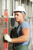 Builder facade plasterer worker with level — Stock Photo