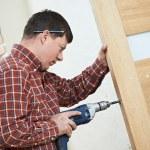 Carpenter at door lock installation — Stock Photo #30038505