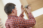Male carpenter at lock installation — Stock Photo