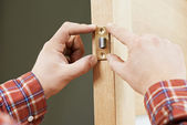 Hand of carpenter at lock installation — Stock Photo