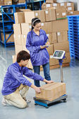 Chinese workers in warehouse — Stock Photo