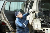 Male auto mechanic repairing body car — Stock Photo