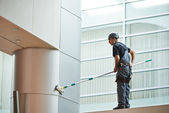 Woman worker cleaning indoor window — Stock Photo