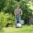 Man mowing lawn in backyard — Stock Photo