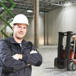 Warehouse worker in front of forklift — Stock Photo #30414911