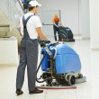 Male worker cleaning business hall — Foto Stock