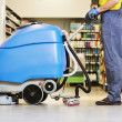 Worker cleaning floor with machine — Stock Photo #30415231