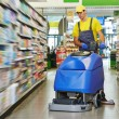Worker cleaning store floor with machine — Stock Photo #30415249