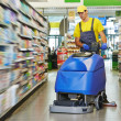 Worker cleaning store floor with machine — Stock Photo