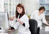 Two Pharmacy chemist women in drugstore — Stock Photo