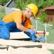 Stock Photo: Carpenter works on roof