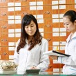 Chinese pharmacy worker in china drugstore — Stock Photo
