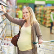 Pregnant woman at milk dairy shopping — Stock Photo #30770037
