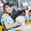 Chinese waitress of restaurant with menu — Stock Photo