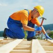 Roofer carpenter works on roof — Stock Photo #30770135
